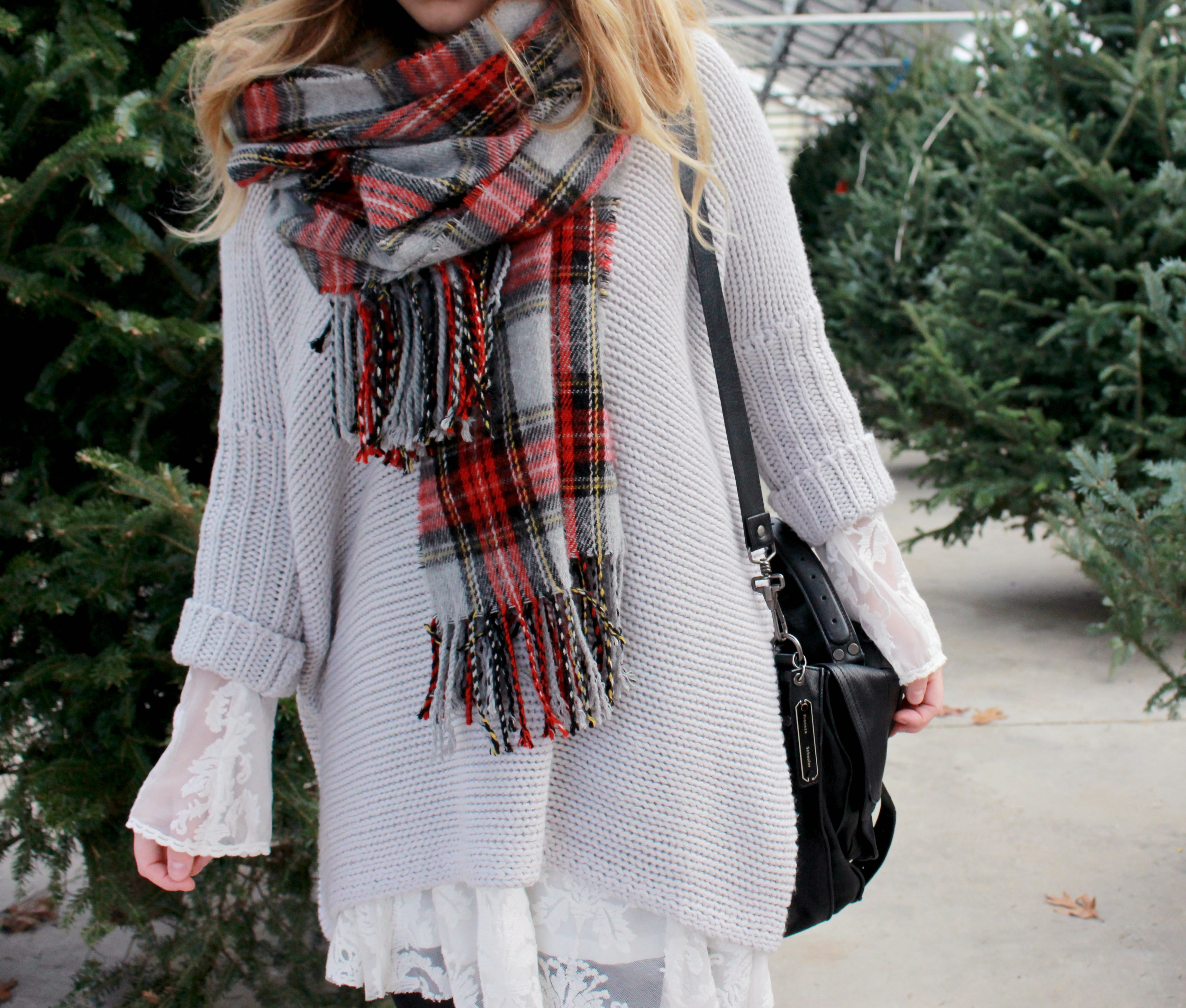 Zoe Namey of blog Zoe With Love styles a Christmas tree shopping look with an oversized sweater over a white last dress and accessorized with a plaid scarf and black hat